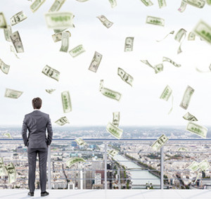 Young businessman with hands in pockets standing on the roof of a business centre and looking at New York. Money falling from above. Back view. Concept of earning money.